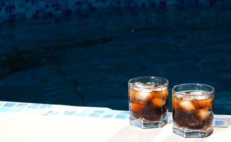 edge of the ice: Two cups of cold cocktails are on the edge of the blue pool