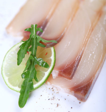 condiment: Fresh white fish decorated with greens, condiment and lime