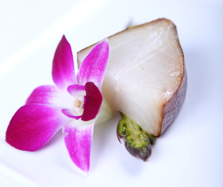the greens: Fresh white fish decorated with greens and flower. Close-up Stock Photo