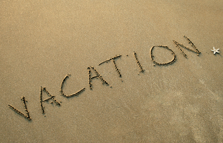 writ: word vacation is writ on the sand of the beach Stock Photo