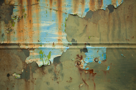 metal corrosion: Close-up view of old damaged metal wall with chipped paint and corrosion