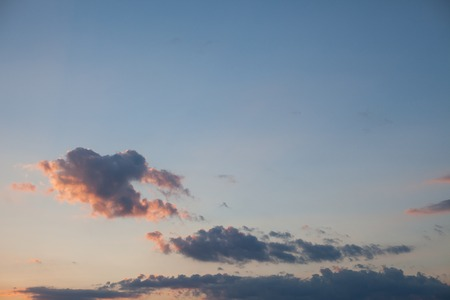pink sunset: Blue sky with pink sunset light and dark fluffy clouds
