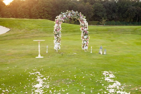 Beautiful floral arch with lots of small pink, purple and white flowers on the green field on the backgroung of the dark forest Stock Photo
