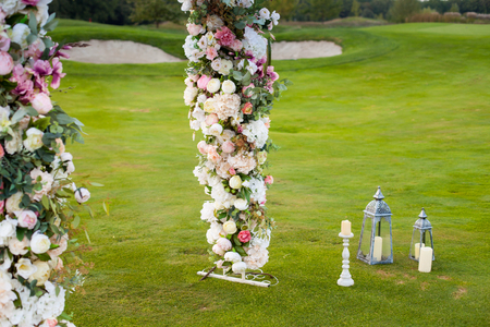 Beautiful floral arch with lots of small pink, purple and white flowers on the green field on the backgroung of the forest with white candles standing nearby