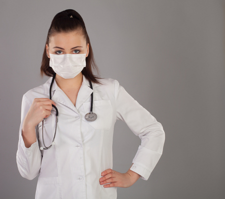 Robe: Nurse in gauze and white robe is against grey background with stethoscope