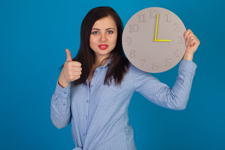 Cute woman with grey clock with yellow arrow in hands is standing against of blue background