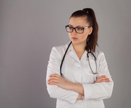 white robe: Nurse in white robe wears stethoscope against of grey background Stock Photo