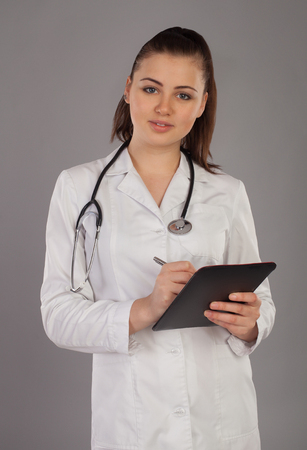white robe: Nurse in white robe is writting something against of grey background