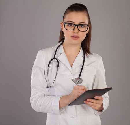 white robe: Nurse in white robe and with stethoscope is writting something in her notes against of grey background