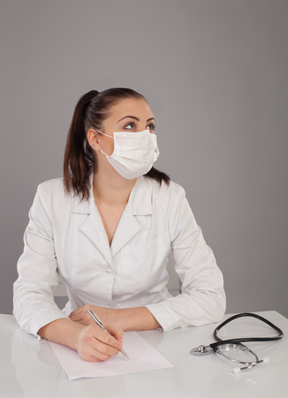 white robe: Nurse in white robe is making a report at the table against of grey background