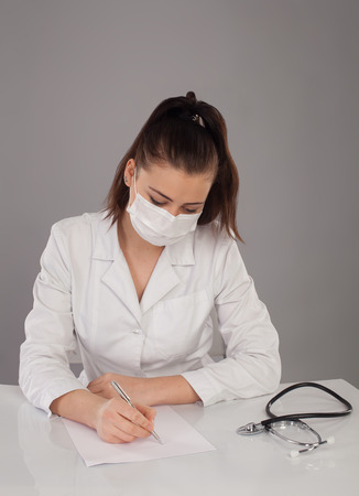 white robe: Nurse in white robe is making a report at the table