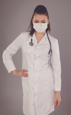 Robe: Nurse in white robe is against grey background