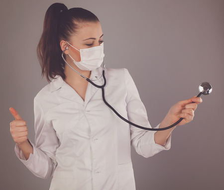 white robe: Nurse in white robe is holding a stethoscope against of grey background Stock Photo