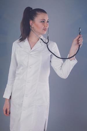 white robe: Nurse in white robe is against grey background