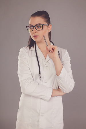 white robe: Nurse in white robe and glasses is looking somewhere against of grey background Stock Photo