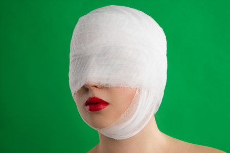 full red: The woman with a bandage on her head and with full red lips is against the background of chromakey. Stock Photo
