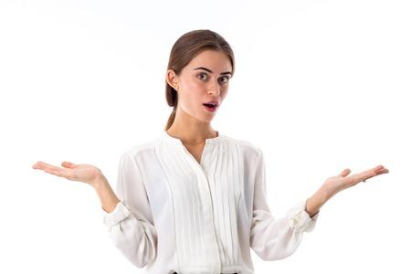 cabeza de mujer: Mujer hermosa joven en la blusa blanca que muestra una sorpresa en el fondo blanco en el estudio Foto de archivo