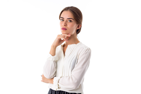 Young beautiful woman in white blouse holding hand near her chin on white background in studio Stock Photo