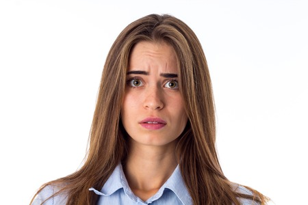 Young beautiful woman with long brown hair in blue shirt looking confused on white backgroung in studio