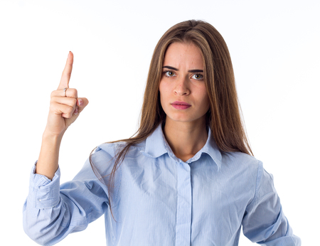 punishing: Young serious woman in blue shirt punishing on white background in studio