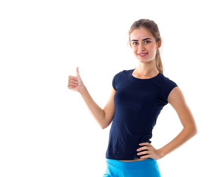 Young smiling woman wearing in blue T-shirt and leggings showing thumb up on white background in studio