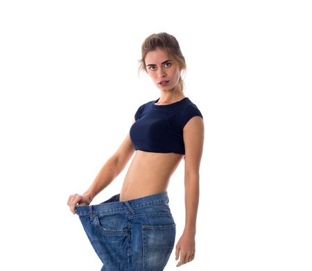 Young woman wearing in blue top and jeans of much bigger size standing on white background in studio Stock Photo