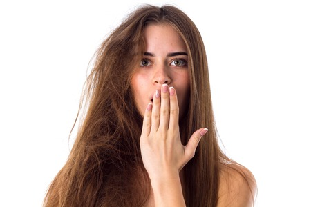 Young disturbed woman with one half of her long brown hair straight and other one tangled on white backgroung