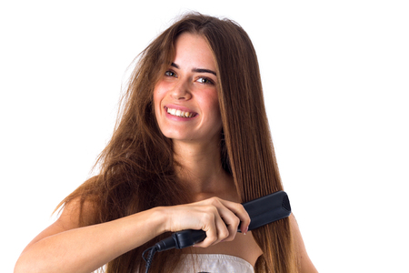 Happy young  woman with long brown hair using hair straightener on white background in studio Stock Photo