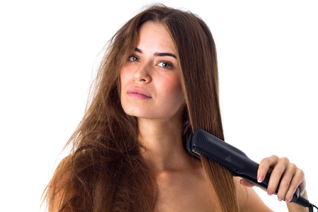 Young  woman with long brown hair using hair straightener on white background in studio Stock Photo