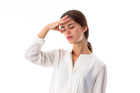 hand on forehead: Young beautiful woman in white blouse holding hand at her forehead on white background in studio Stock Photo