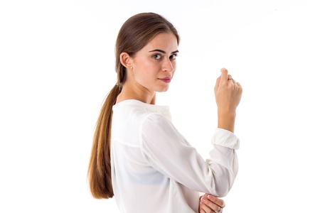 ponytail: Young pretty woman with pony-tail wearing a white blouse on white background in studio
