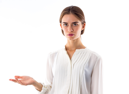 Young beautiful woman in white blouse showing her great perplexity on white background in studio