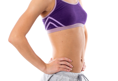 Young sportive woman in purple sports top and grey shorts showing her abdominals on white background in studio