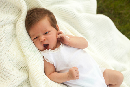 yawing: Little cute baby in white clothing lying and yawing on the white blanket on the green grass