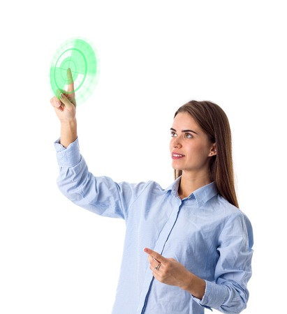 Young nice woman with long hair in blue shirt pointing up on white backgroung in studio Stock Photo