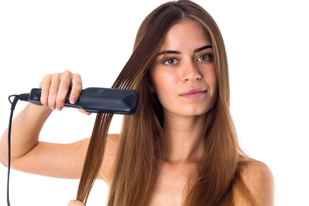 straightener: Young beautiful woman with long brown hair using hair straightener on white background in studio