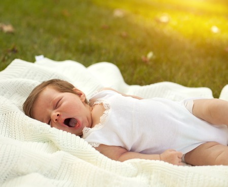 yawing: Little charming baby in white clothing lying and yawing on the white blanket on the green grass