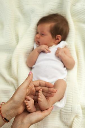 white blanket: Hands holding little cute babys legs on white blanket
