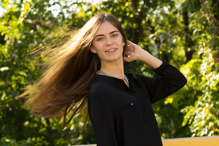 silver hair: Young pretty woman in black blouse with silver necklace touching her long hair on the background of green trees
