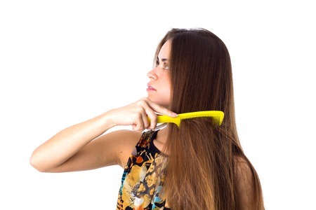Young beautiful woman in colored shirt combing her long brown hair using yellow hair brush on white background in studio Stock Photo