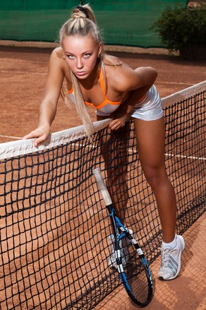 tennis skirt: Athletic woman in bra and short skirt trying to get over a tennis net