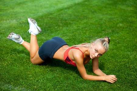 Beautiful young woman in a sports suit lying on a green soccer field at the stadium