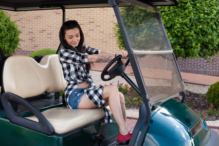 briefs: Beautiful woman with a tottoo in short jeans briefs is sitting on a green golf cart.