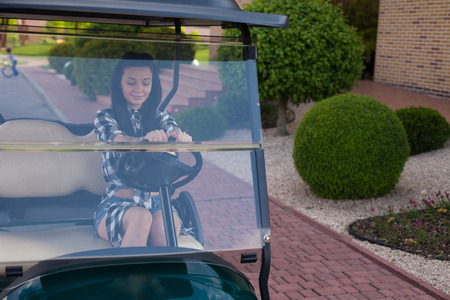 golf cart: Beautiful woman with a tottoo in  plaid shirt is sitting on a golf cart.