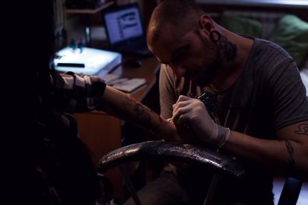 Tattoo artist is implanting coloring pigmant into elected area
