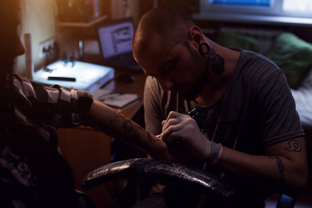 implanting: Tattoo artist is implanting coloring pigmant into elected area