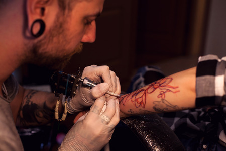 sterilized: Tattoo artist is inserting ink into the skin using sterilized nitrile gloves and tattoo machine