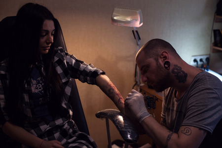 implanting: Tattoo artist is implanting coloring pigmant in womans hand