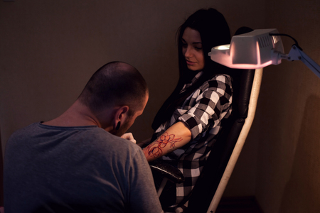 indelible: Woman is sitting on the chair and getting tattoo in tattoo salon