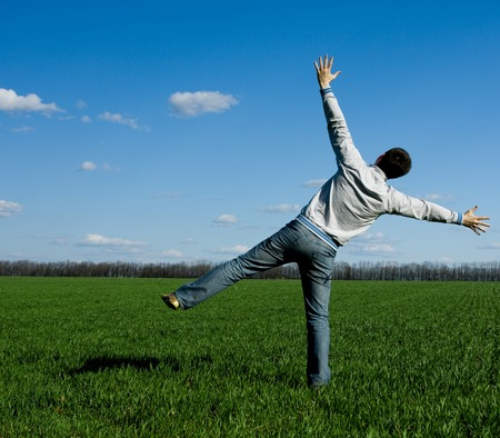 human energy: young happy man standing on the green field Stock Photo
